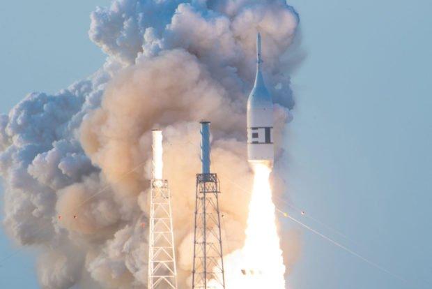 Vapor fills the sky as a rocket blasts off.