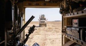 A military vehicle drives through dirt.