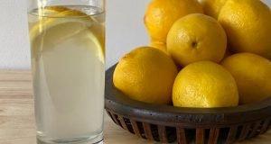 A basket of lemons sits beside a glass of lemonade.